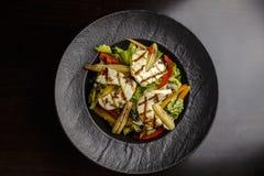Halloumi salad in black bowl stock photos
