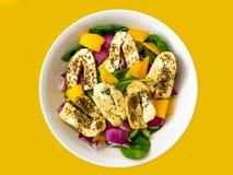 Halloumi-Salat auf gelbem Hintergrund lizenzfreies stockbild