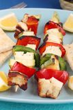Halloumi souvlaki. Two skewers of vegetarian halloumi with red and green peppers and zucchini. Served with lemon and pitta bread Royalty Free Stock Photography