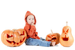 Halloveen small boy sits surrounded by pumpkins on Stock Images