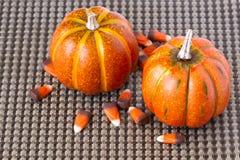 Hallowee-Kürbise und Süßigkeitsmais auf einem braunen gesponnenen Hintergrund stockbild