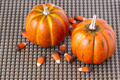 Hallowee Pumpkins and candy corn on a brown woven background. Two orange pumpkins and candy corn decorations on a woven background stock image