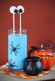 Halloweem Blue Smoothie with Marshmallow Eyes Drink with cauldron. Stock Photo