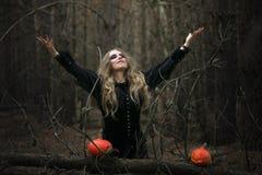 halloween красивая девушка ведьмы в черном платье в лесе Стоковая Фотография