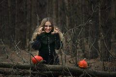 halloween красивая девушка ведьмы в черном платье в лесе Стоковые Изображения