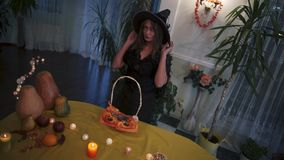 halloween Красивая девушка пробуя на шляпе ` s ведьмы видеоматериал