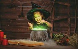 halloween маленький ребенок ведьмы варя зелье в котле с Стоковое Изображение