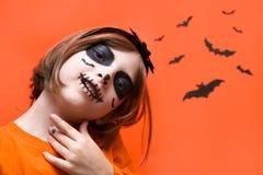 halloween Портрет девушки составленной на оранжевой предпосылке стоковая фотография