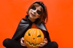 halloween Портрет девушки составленной на оранжевой предпосылке стоковое изображение