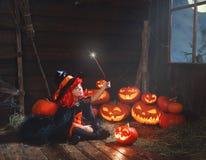 halloween ребенок ведьмы с волшебными палочкой и тыквами Стоковая Фотография