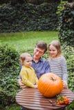 halloween счастливый Отец и 2 дочери смотрят сторону отрезанную в тыкве на хеллоуин снаружи стоковые фото