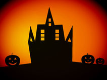 Halloween. Black castle  with three  pumpkins, over orange  background Stock Images