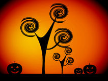 Halloween. Black pumpkins with abstract trees over orange background Stock Image