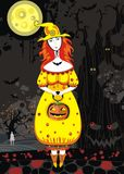 Halloween. Beautiful young witch with a pumpkin on a cemetery at night Stock Image