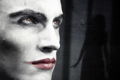 Halloween. Face of vampire on a dark grungy background with woman shadow Stock Image