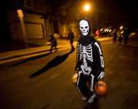Halloween. Boy trick or treating on Halloween night. He's dressed in skeleton costume walking down the street with a candy bucket in each hand Stock Image