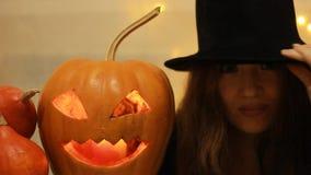 Halloween Abóbora Mulher no chapéu negro expressa emoções com olhos grandes - surpresa, medo, susto fim do retrato video estoque