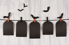 Halloween advertising mock up. Blank black sale labels tomb hanging on clothespins, flock bats and white wooden plank background. Stock Images