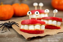 Halloween apple, marshmallow, peanut butter monster teeth over wood Stock Photo