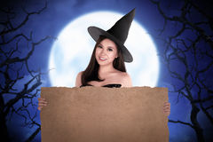 Halloween asian witch holding parchment paper Stock Photos