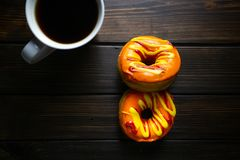 Halloween and Autumn colored tasty colorful donuts served for breakfast on a kitchen table with piping hot coffee royalty free stock photo