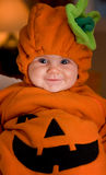 Halloween baby. Baby girl dressed up as pumpkin for Halloween with smile
