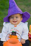 Halloween Baby. Smiling baby wearing purple witches hat and peek a boo costume Royalty Free Stock Photo