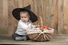 Halloween baby with basket of apples. Seated on an old wooden floor Royalty Free Stock Image