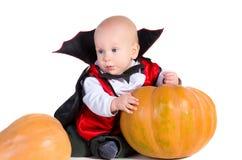 Halloween-Baby im Dracula-Mantel mit dem Pumpking lizenzfreie stockbilder