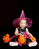 Halloween baby witch with a carved pumpkin. Over black background royalty free stock photos