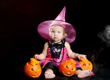 Halloween baby witch with a carved pumpkin. Over black background royalty free stock photo