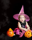 Halloween baby witch with a carved pumpkin Stock Photo