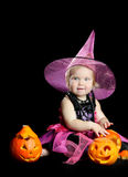 Halloween baby witch with a carved pumpkin Stock Images