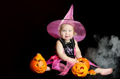 Halloween baby witch with a carved pumpkin Stock Photos
