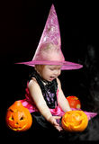 Halloween baby witch with a carved pumpkin Royalty Free Stock Images