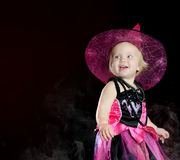 Halloween baby witch with a carved pumpkin. Over black background with smoke stock image