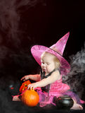 Halloween baby witch with a carved pumpkin Stock Image
