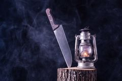 Halloween background of big knife and burning old oil lamp on wood log in forest royalty free stock photography