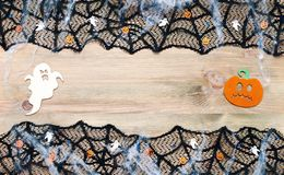 Halloween background. Black cobweb lace border and Halloween decorations on the wooden background with free space. For Halloween text royalty free stock photo