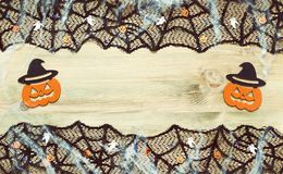 Halloween background. Black cobweb lace border and Halloween decorations on the wooden background with free space. For Halloween holiday text royalty free stock image