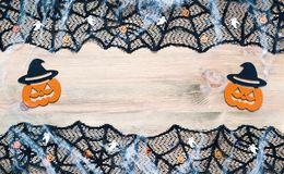 Halloween background. Black cobweb lace border and Jack-o-lantern decorations on the wooden background. With free space for Halloween text royalty free stock photography