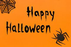Halloween background. Text Happy Halloween Black paper spider and spiderweb on orange background Royalty Free Stock Images