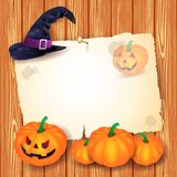 Halloween background with blank paper, hat and pumpkins Royalty Free Stock Images