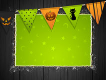 Halloween background with bunting on wood. Halloween background with green torn paper and bunting on black wood Royalty Free Stock Image