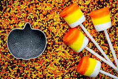 Halloween background - candy corn marshmallow pops on colored su Stock Photography