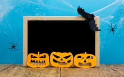 Halloween background concept. Blackboard with decor paper cut jack O pumpkin faces on wooden table and blue backdrop. Halloween background decoration holiday royalty free stock photos