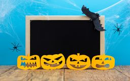 Halloween background concept. Blackboard with decor paper cut jack O pumpkin faces on wooden table and blue backdrop. Halloween background decor holiday concept royalty free stock images