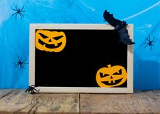 Halloween background concept. Blank blackboard with decor paper cut jack O pumpkin faces on wooden table and blue backdrop. Halloween background decor holiday stock images