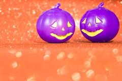 Halloween background concept. purple jack O pumpkin faces on bright glitter orange backdrop. Halloween background decor holiday concept. purple jack O pumpkin stock photos