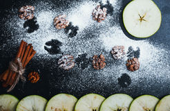 Halloween background with flying bats. Sliced apple, cinnamon st. Icks and walnuts over dark background. Top view Stock Images